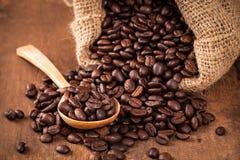 Chicco di caffè sulla tavola di legno con il cucchiaio ed il sacco Immagine Stock Libera da Diritti