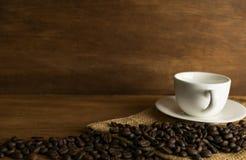 Chicco e tazza di caffè di caffè sul bordo di legno davanti a marrone Fotografia Stock Libera da Diritti
