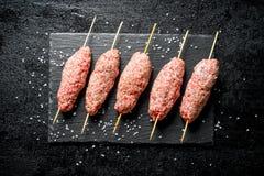 Chiche-kebab cru du boeuf hach? sur un conseil en pierre avec des morceaux de sel images libres de droits