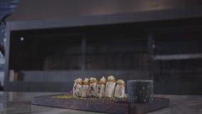 Chiche-kebab délicieux enveloppé dans le pain pita de lavash se trouvant sur un conseil en bois sur la table dans la fin moderne  banque de vidéos
