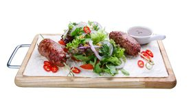 Chiche-kebab d'agneau avec la salade mixte sur un conseil en bois photos libres de droits