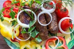Chiche-kebab de Lula de porc et de boeuf d'un plat à l'oignon, au paprika et aux brins coupés de l'aneth, du persil et des tomate Photos libres de droits
