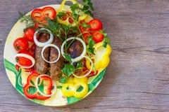 Chiche-kebab de Lula de porc et de boeuf d'un plat à l'oignon, au paprika et aux brins coupés de l'aneth, du persil et des tomate Images libres de droits