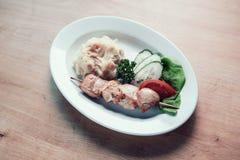 Chiche-kebab de porc, purée de pommes de terre et tranches de légumes frais dans un plat photo stock
