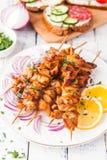 Chiche-kebab de poulet avec un citron et un oignon sur un fond en bois images libres de droits