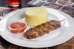 Chiche-kebab de viande avec de la purée de pommes de terre et la sauce rouge images stock