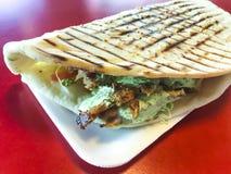 Chiche-kebab turc épicé de doner rempli de la viande rôtie, de salade fraîche et de sauce à ail en tortilla grillée photos libres de droits