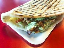 Chiche-kebab turc épicé de doner rempli de la viande rôtie, de salade fraîche et de sauce à ail en tortilla grillée image libre de droits