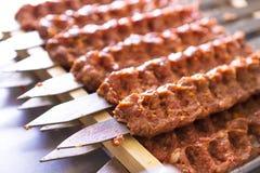 Chiches-kebabs chevronnés d'Adana sur des brochettes attendant pour être fait cuire image stock