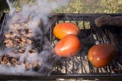 Chiches-kebabs et tomates sur un gril de charbon de bois Images stock