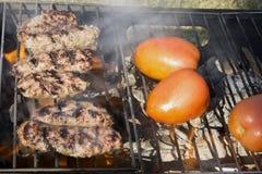 Chiches-kebabs et tomates sur un gril de charbon de bois Image stock