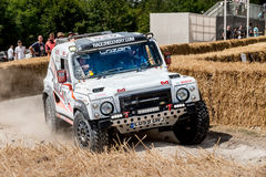 Chichester, West Sussex, UK - June 29, 2014: Landrover rally vehicle slides around corner with hay bails separating onlookers from Stock Image