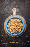 Chick peas, hummus in blue bowl with water on rustic wooden background Stock Images