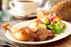Chicken. A piece of roasted chicken thigh topped with mushroom sauce with mashed potatoes and salad at the side Royalty Free Stock Images