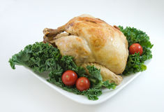 Chicken. Roasted chick on plate garnished with kale and cherry tomatoes Stock Photos