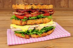 Chicken And Bacon Double Decker Sandwich. On a wood background Stock Photos