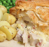 Chicken & Bacon Pie. Chicken and bacon pie with filo pastry topping and served with new potatoes and peas. Seasoned with sea salt and freshly ground pepper Royalty Free Stock Photography