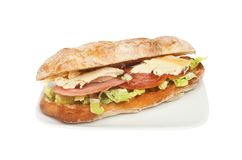 Chicken and bacon roll. Chicken, bacon and lettuce in a ciabatta roll on a plate isolated against white royalty free stock image