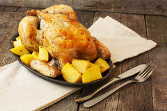 Chicken baked with potatoes on a cast iron pan on a wooden backg Royalty Free Stock Photo
