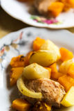 Chicken baked with slices of potato and a pumpkin on the plate Stock Photos