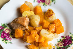 Chicken baked with slices of potato and a pumpkin on the plate Royalty Free Stock Image
