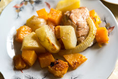 Chicken baked with slices of potato and a pumpkin on the plate Stock Photo