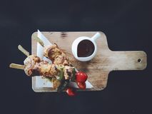 Chicken BBQ with spicy sauce. On the wooden plate, top view and black background stock photography