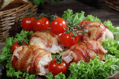 Chicken beaters in bacon submitted on leaves of salad with fresh. Tomatoes stock image