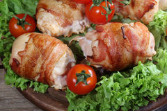 Chicken beaters in bacon submitted on leaves of salad with fresh. Tomatoes stock photography