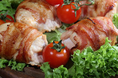 Chicken beaters in bacon submitted on leaves of salad with fresh. Tomatoes stock images