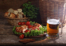 Chicken beaters in bacon submitted on leaves of salad with fresh. Tomatoes and beer in a transparent mug stock photography
