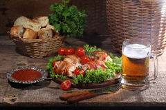 Chicken beaters in bacon submitted on leaves of salad with fresh. Tomatoes and beer in a transparent mug stock images