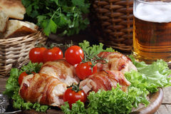 Chicken beaters in bacon submitted on leaves of salad with fresh. Tomatoes and beer in a transparent mug royalty free stock images