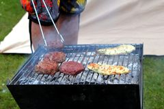 Chicken and beefburgers cooking on a traditional lumpwood charco. Al barbecue Stock Images