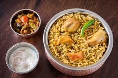 Chicken biryani with salad. Closeup view from the top of delicious Indian chicken biryani served in authentic copper utensils with traditional sides, raita and stock image