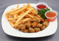 Chicken Bits and Fries Combo. Plated meal of Chicken nuggets and French fries with dipping sauces royalty free stock photo