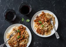 Chicken bolognese spaghetti and glasses of red wine on dark background, top view. Delicious lunch in a mediterranean style, top vi Stock Photos
