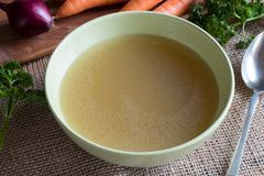 Chicken bone broth in a green soup bowl. With carrots, onions and parsley in the background stock images
