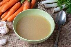 Chicken bone broth in a green soup bowl. With fresh vegetables in the background royalty free stock photo