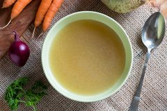 Chicken bone broth in a green soup bowl, top view. Chicken bone broth in a green soup bowl with vegetables in the background stock photos