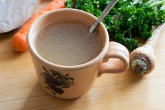 Chicken bone broth in a mug with vegetables in the background. Chicken bone broth in a mug with fresh vegetables in the background stock photo