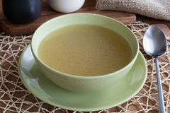 Chicken bone broth served in a green soup bowl.  Stock Photo