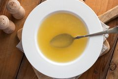 Chicken bone broth in a soup plate. Top view royalty free stock photography
