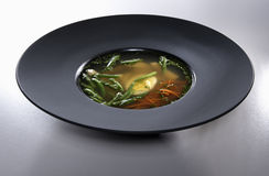 Chicken bouillon in black plate isolated on white background. Chicken soup with eggs, carrot and asparagus seasoned with fresh parsley in black plate isolated on royalty free stock photo