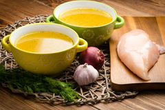 Chicken bouillon in the bowls on the rustic wooden background. Chicken bouillon in thebowl on the rustic brown wooden background Royalty Free Stock Photos