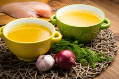 Chicken bouillon in the bowls on the rustic wooden background. Chicken bouillon in the yellow and green bowls on the rustic wooden background Royalty Free Stock Images
