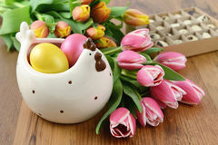 Chicken bowl with easter eggs and bunch of tulips around Stock Photos