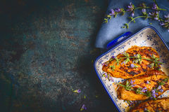 Chicken breast in cooking dish with fresh herbs on dark blue rustic background, top view Stock Photos