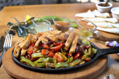 Chicken breast cuts fajitas and vegetables. Chicken breast fajitas with yogurt and vegetables and sause on wooden table Royalty Free Stock Image
