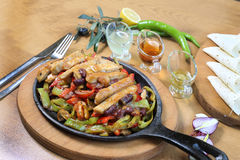 Chicken breast cuts fajitas and vegetables. Chicken breast fajitas with yogurt and vegetables and sause on wooden table Stock Photo